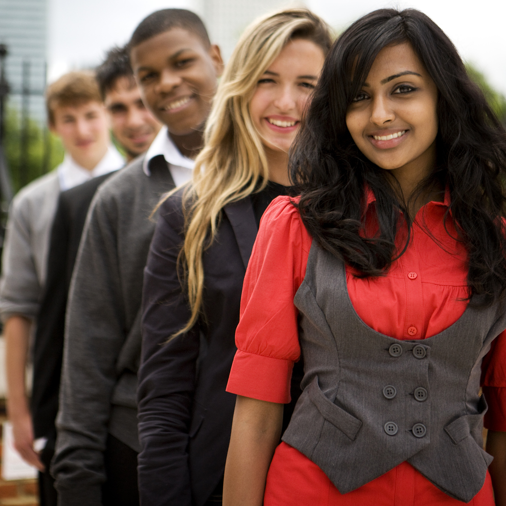 A group of diverse young professionals standing outside. The first is a young Indian lady wearing a bright red top and grey vest