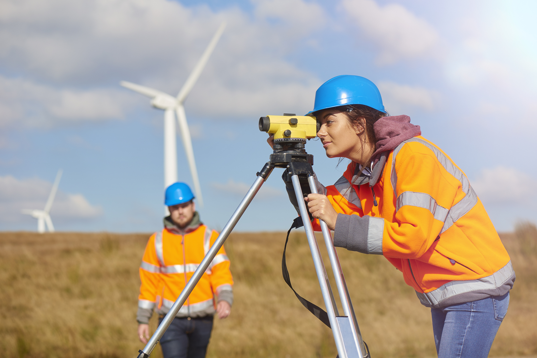 Female engineer wearing a hard hat and safety jacket, standing in front of windmills and using engineering equipment. Her male partner is standing behind her outside.