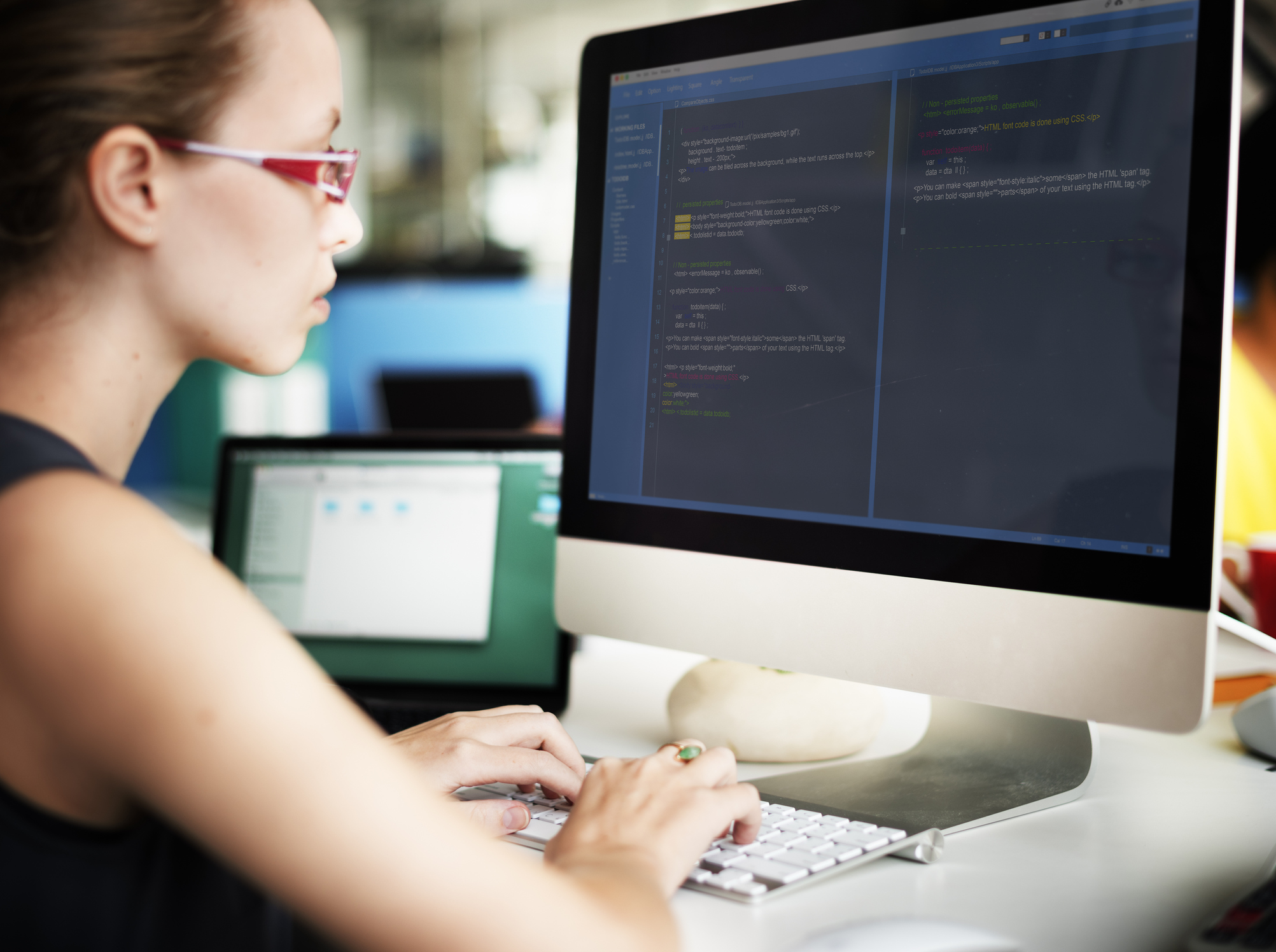 Female professional with red glasses sitting in front of a monitor, typing computer science coding