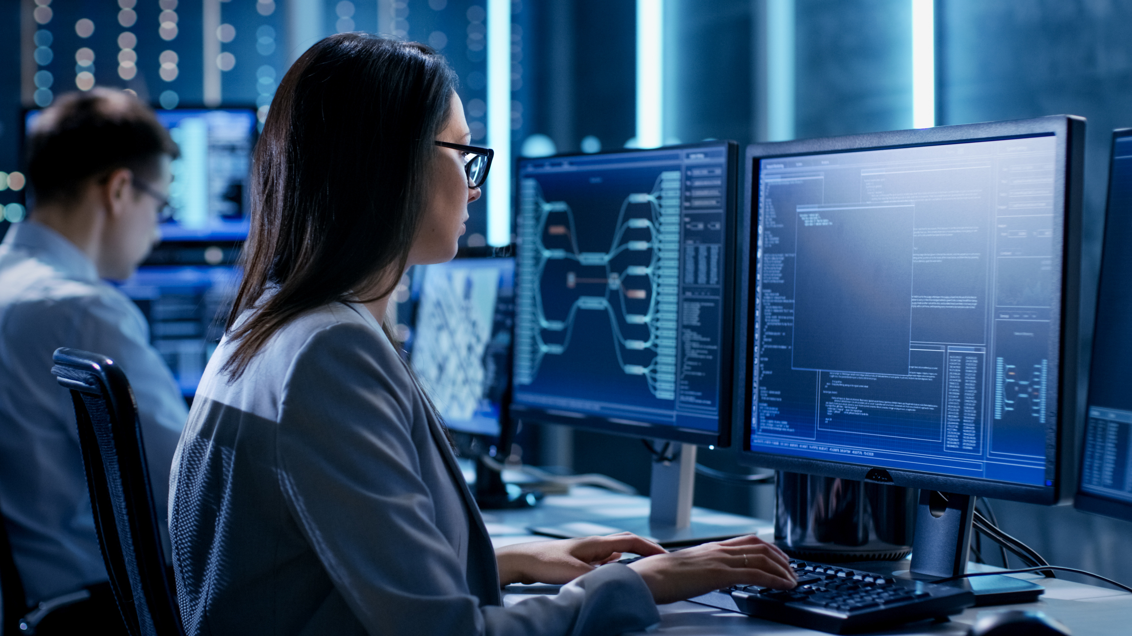 Female cybersecurity professional sitting at a computer working on coding