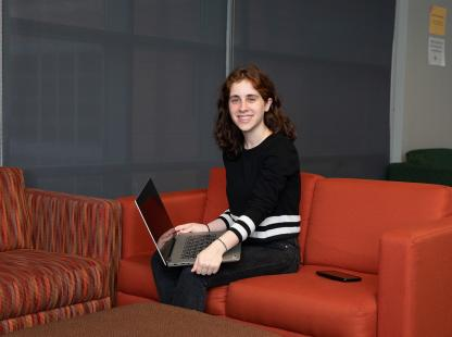 Photo of a student sitting in a lounge area