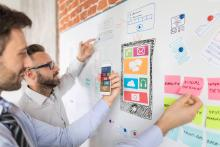 Two male professionals standing at a white board brainstorming ideas for social media design and web design. The white board has an image of an iPhone with colorful notes and ideas